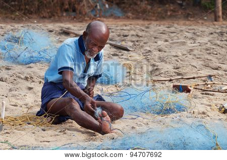 Indian Fisherman With Fishing Net On Beach In Varkala