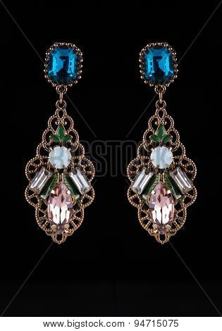 gold earrings with jewels on the black