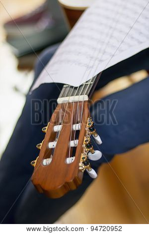 Acoustic Guitar's Fretboard Head And Musical Scores On A Fretboard