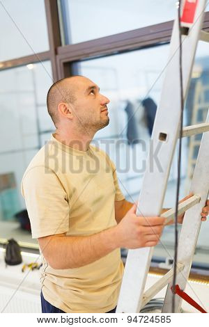 Electrician man helping his teammate on ladder. poster