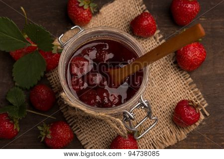 strawberry jam with fresh strawberries on a dark wooden table poster