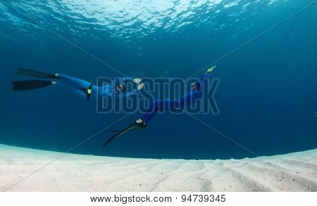 Two freedivers having fun over the sandy sea bottom
