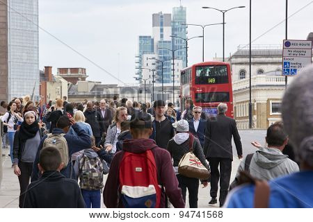 LONDON, UK - JUNE 23: Busy pavement on London Bridge, with red Routemaster bus in the background. June 23, 2015 in London.