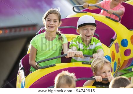 Boy and Girl on a thrilling roller coaster ride at an amusement park