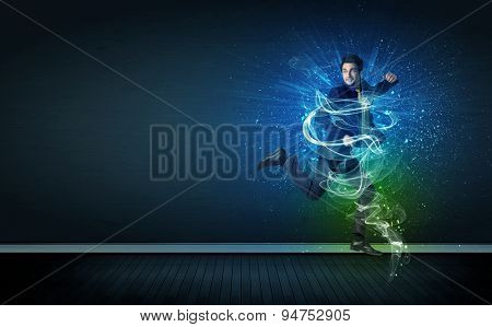 Talented cheerful businessman jumping with glowing energy lines on background poster
