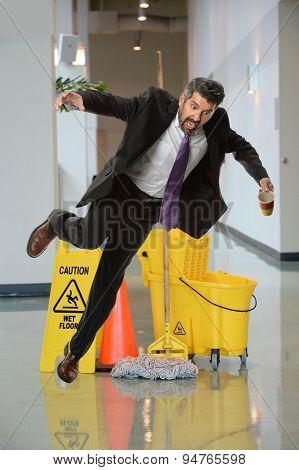 Businessman falling on wet floor inside office building