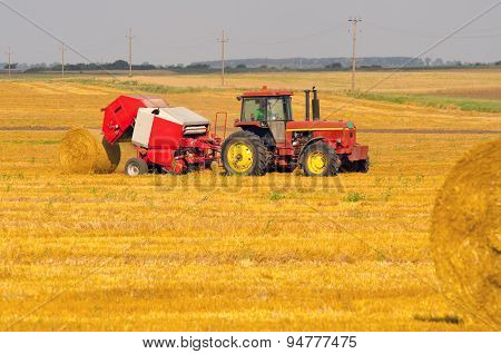Tractor Making Hay Bales On Agricultural Field