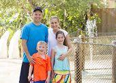 Beautiful young family enjoying a day at an outdoors amusement park poster
