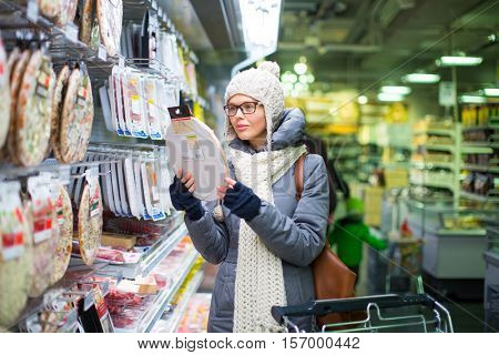 Beautiful young woman shopping in a grocery store/supermarket on a cold winter day(color toned image)
