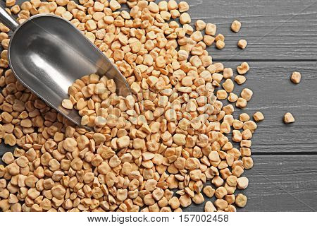 Metallic scoop with grass pea buckwheat on wooden background