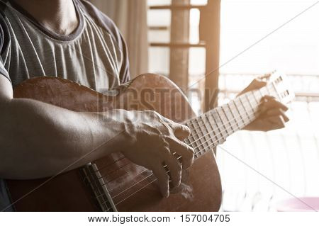 Practicing in playing guitar. Handsome young men playing guitar in homevintage effect.