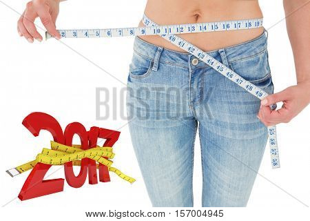 Woman measuring her waist against digitally generated image of new year with tape measure