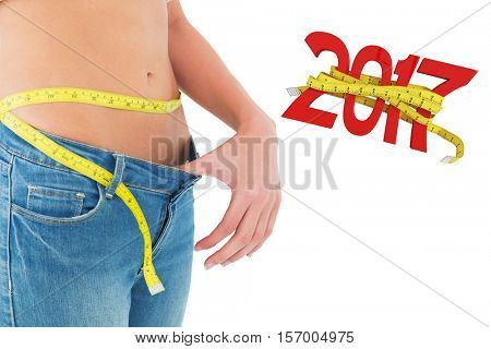 Mid section of woman measuring waist in a big sized jeans against digitally generated image of new year with tape measure