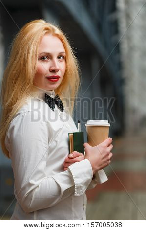 Beautiful ginger with long hair holding notebook and coffee in lobby of building
