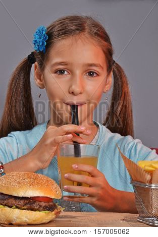 Little girl eating orange soda and eating burger and fried potatoes.