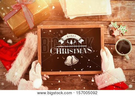 Santa claus holding a slate with merry christmas text against merry christmas message