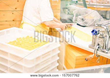 Middle age woman prepares homemade tortellini in italian pasta factory - Handmade manufacturing with organic eggs and bio wheat flour - Soft focus on hand cutting puff pastry - Warm filter