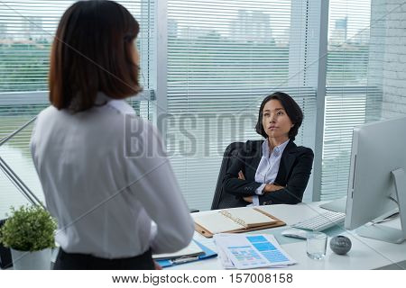 Confident Vietnamese business woman listening to ideas of employee