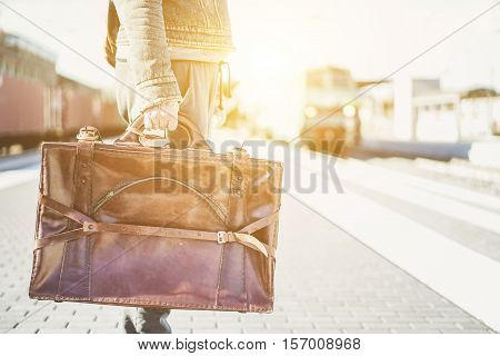 Close up of a man traveler waiting train for journey at train station - Hipster traveler holding vintage leather cow hide suitcase - Travel concept - Warm vintage filter with sun flare