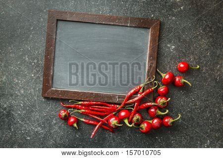 Chalkboard and red chili peppers. Top view.