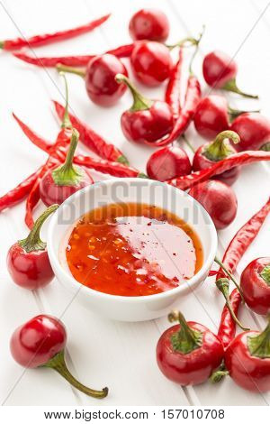 Red chili peppers and chili sauce on white table.