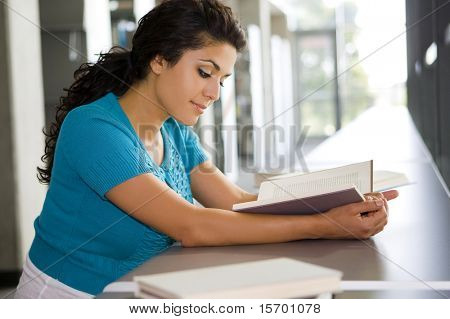 Young woman reading a book at school