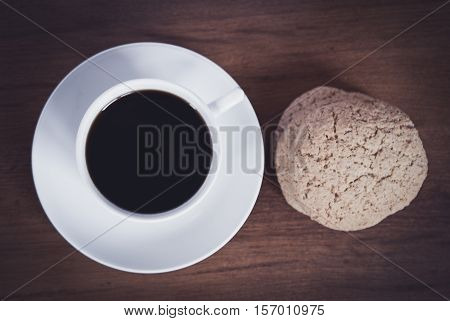 fresh cup of coffee and biscuits for breakfast on a wooden table