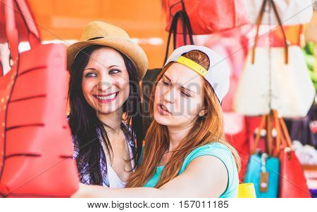 Young cheerful women at flea market buying fashion bags - Best female friends having fun and shopping in the old town center - New trends accessories addiction concept - Vivid color tones editing