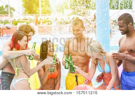 Group of multiracial people partying and having fun in swimming pool - Young friends having party drinking cocktails and beers - Resort vacation concept - Main focus on black hair girl - Warm filter