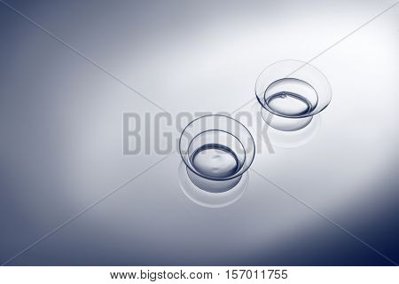 Pair of contact lenses on smooth light background, close up view. Medicine and vision concept
