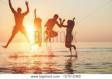 Silhouettes of young friends having fun in water for beach party - Group of happy people dancing and jumping inside sea on beautiful summer sunset - Joyful friends concept - Soft focus on left girl