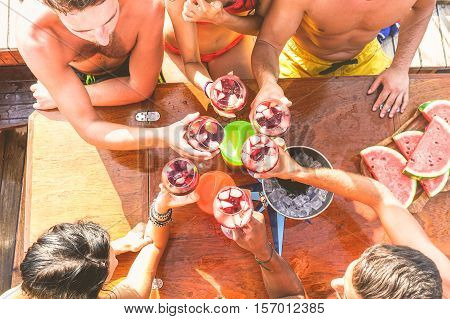 Happy friends having fun outdoors in boat party - Young people enjoying summer vacation together toasting wine with fruit - Youth and friendship concept
