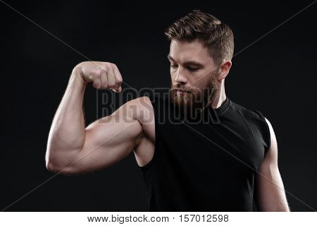 Fitness man demonstrates bicep. looking at bicep. in studio. isolated dark background