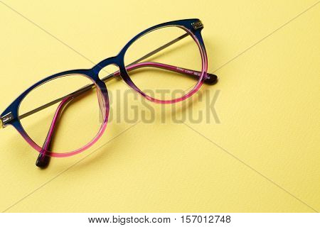 Blue-pink glasses on yellow background