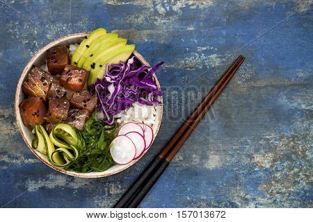 Hawaiian tuna poke bowl with seaweed avocado red cabbage slaw radishes and black sesame seeds. Top view overhead flat lay copy space
