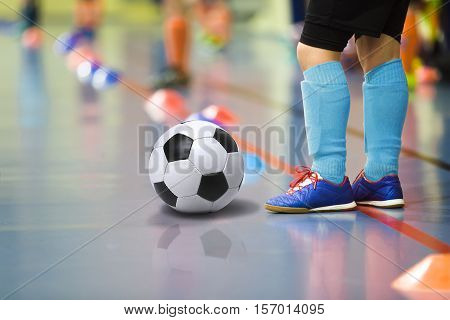 Children training soccer futbal indoor gym. Young boy with soccer ball training indoor football. Little player in light blue sports socks