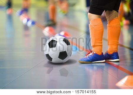 Children training soccer futbal indoor gym. Young boy with soccer ball training indoor football. Little player in light orange sports socks