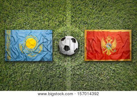 Kazakhstan vs. Montenegro flags on a green soccer field, 3d rendering, 3d rendering