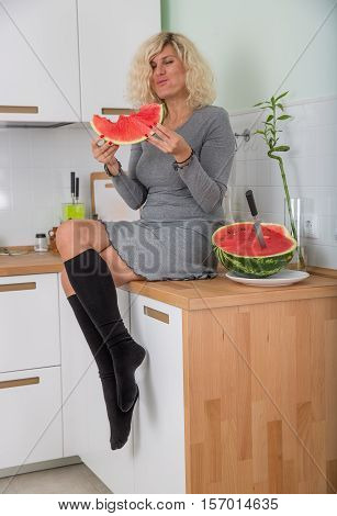Beautiful girl is eating watermelon on the kitchen
