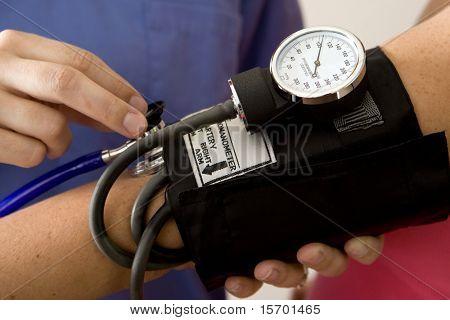 Médico ou enfermeiro, tendo a pressão arterial de um paciente
