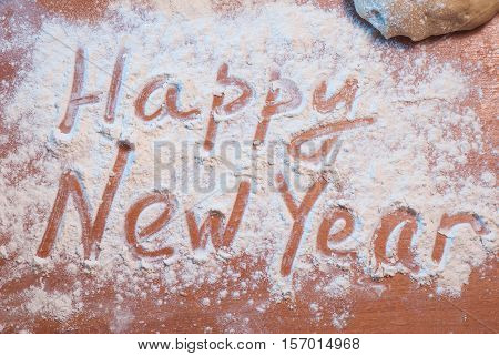 Happy New Year written on the flour, Christmas background, preparing food, rolling pin, knife and wooden table