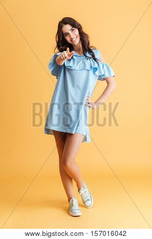 Full length portrait of a young happy woman in blue dress pointing finger at camera over orange background