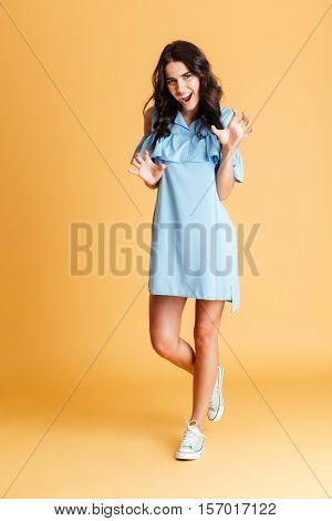 Full length of a playful brunette woman in dress posing and gesturing with hands isolated on a orange background