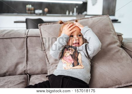 Funny baby on sofa. hends on head