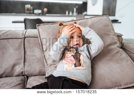 Pretty baby on sofa. hends on head. looking away