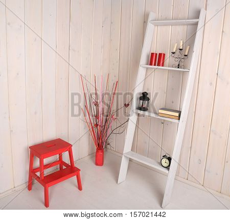 Decorative white staircase with objects in the interior. Red vase with dry twigs and red stand on the floor