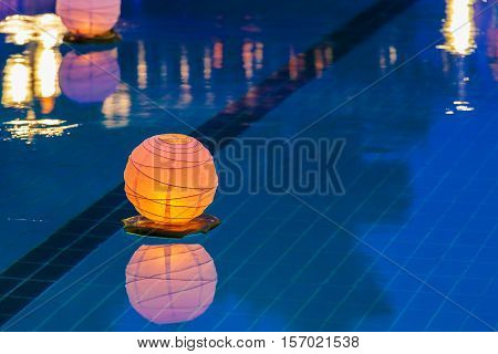 Floating orange water lantern in the pool