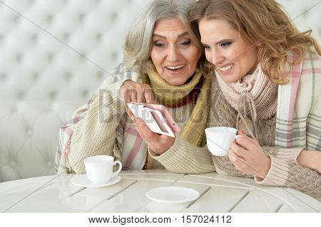 Portrait of senior mother and her daughter drinking tea and looking at something on smartphone