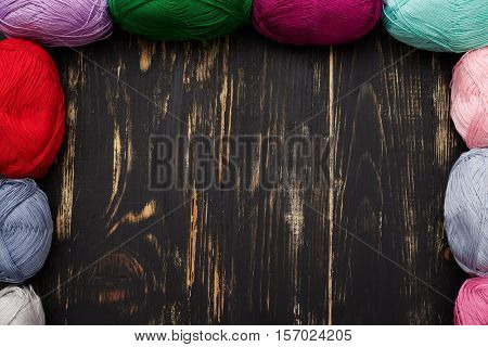 Top view of dark wooden table with empty space in the middle and skeins of different colors lying on sides