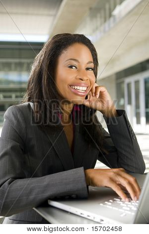 Business woman working outside on her computer